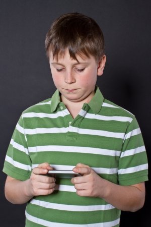 12 13 years: Teen plays on the phone on a black background