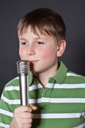 Teen singing into a microphone on a black background Stock Photo - 17478288
