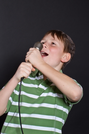 Teen singing into a microphone on a black background Stock Photo - 17478284