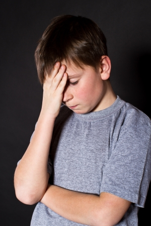 12 13 years: boy holding his head on a black background