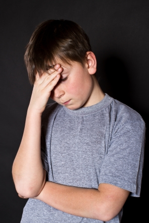 boy holding his head on a black background photo