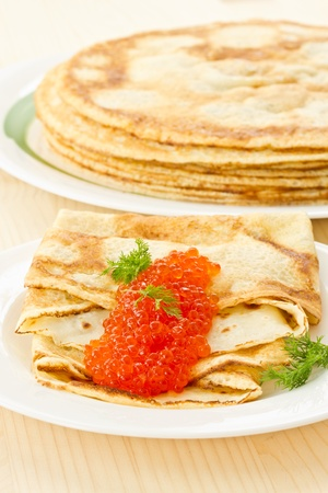 pancakes with red caviar on a plate photo