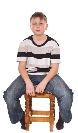 12 13 years: boy sitting on a stool on a white background Stock Photo