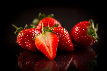 medium shot: ripe red strawberries on a black background