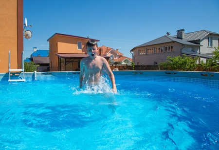 boy jumping in the pool in the hot summer photo