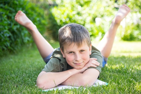 boy with a book on the grass on a sunny day photo