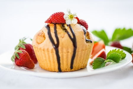 strawberry muffins with chocolate sauce on a white plate photo