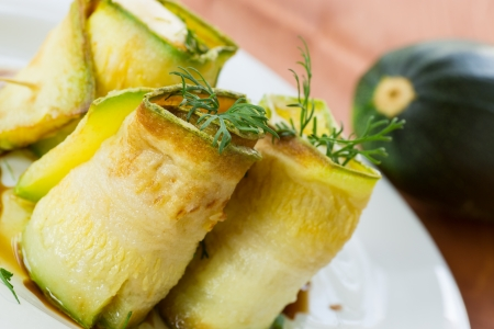Zucchini rolls with a filling on a white plate photo