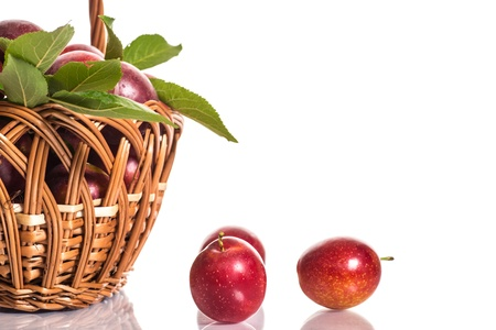 Fresh ripe plums in a basket on a white background photo