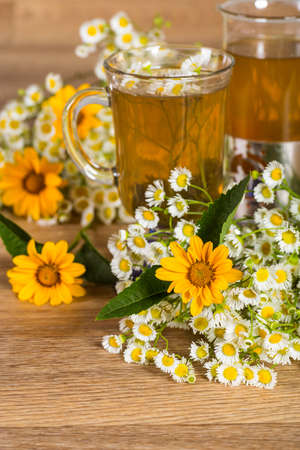 chamomile tea with a bouquet of daisies on the table Stock Photo - 21359321
