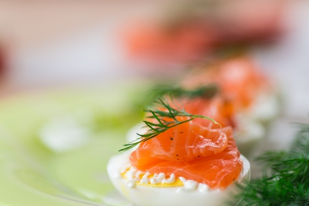 Boiled eggs with salted salmon and herbs photo