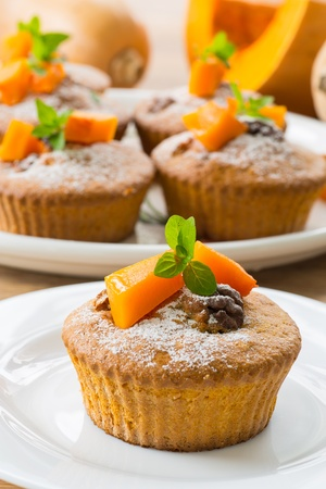 sweet pumpkin muffins with walnuts and powdered sugar photo