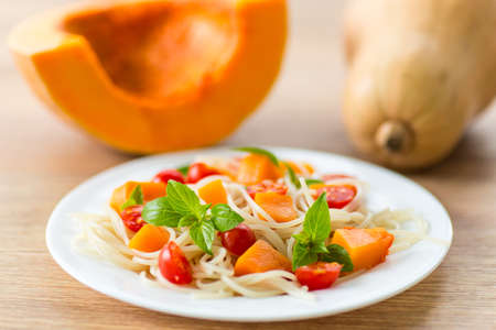 spaghetti with chunks of pumpkin and tomatoes photo
