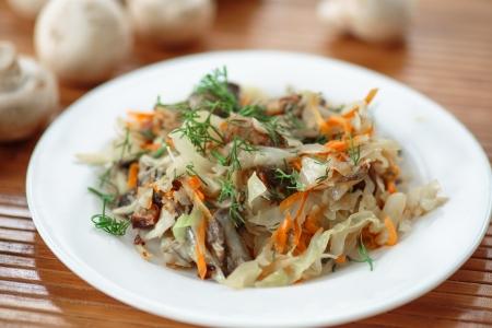 braised mushrooms: plate of braised cabbage with mushrooms on the table