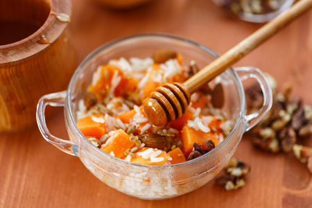 boiled rice with pumpkin, honey and nuts photo