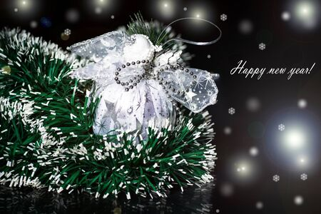 Christmas ball with green garland on a black background photo