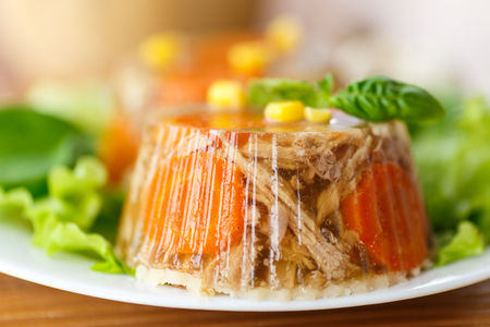 jellied meat with carrots garnished with vegetables photo