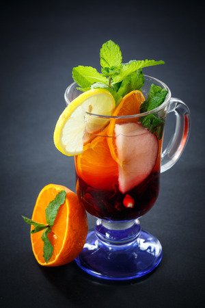 hot fruit tea with fruit and mint on black background