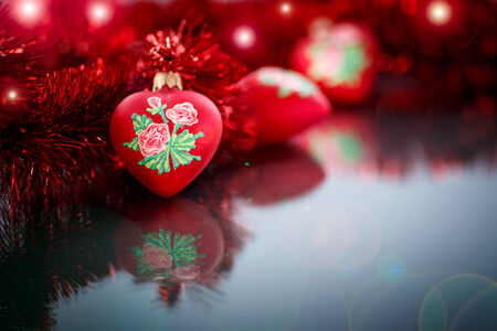 Christmas red hearts with red garland on a black background photo