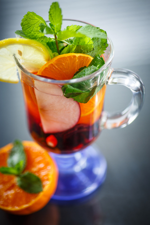hot fruit tea with fruit and mint on black background photo