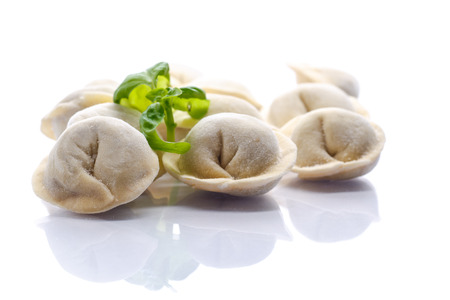 uncooked meat dumplings on a white background with basil photo