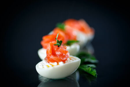 boiled egg with salty salmon on black  photo
