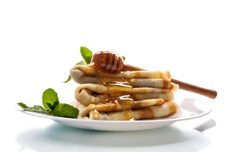 pancakes with honey and mint on a white background photo