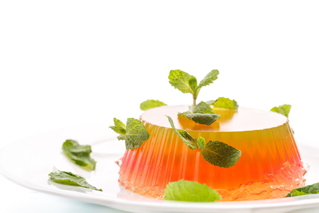 fruit jelly with mint on a plate on white background photo