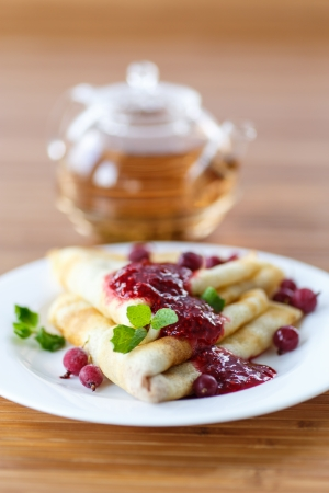 pancakes with jam and berries on a plate photo