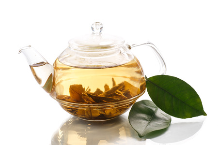 green tea in a teapot on a white background