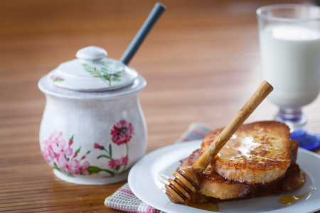 sweet toast with honey and milk on a wooden table photo