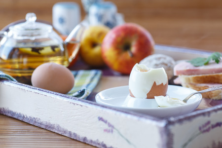 breakfast with a boiled egg, tea, sandwiches and fruit photo