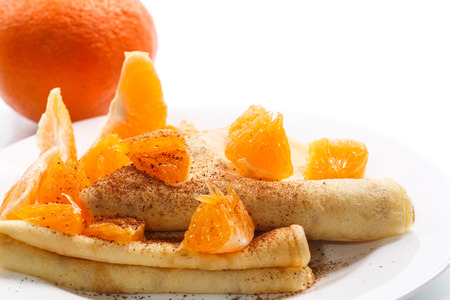 pancakes with mandarins and cinnamon on white background photo