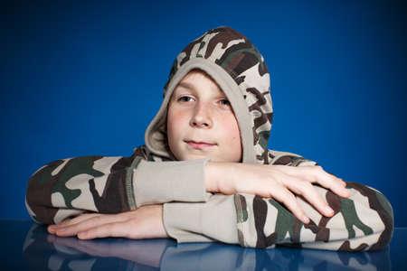 Portrait of a teenage boy on a blue background photo