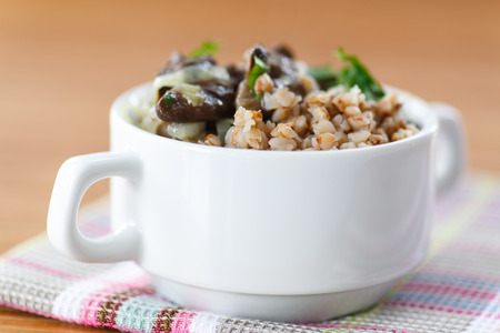 Boiled buckwheat with mushrooms on a wooden table photo