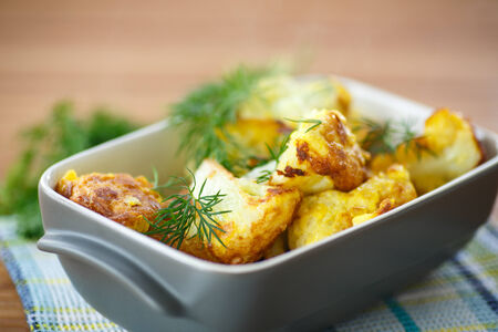 cauliflower fried in batter with dill on a wooden table photo