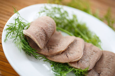 boiled beef tongue sliced ??on a plate with dill photo