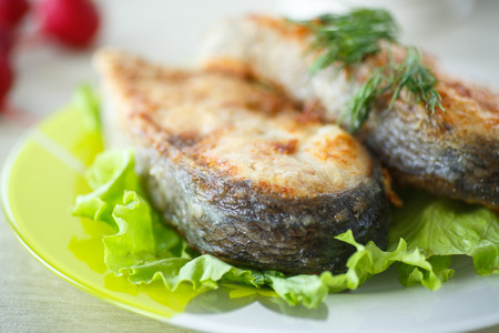 fried carp in large chunks on a plate with salad photo