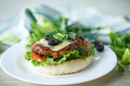tasty hamburger with lettuce and tomato on a plate photo