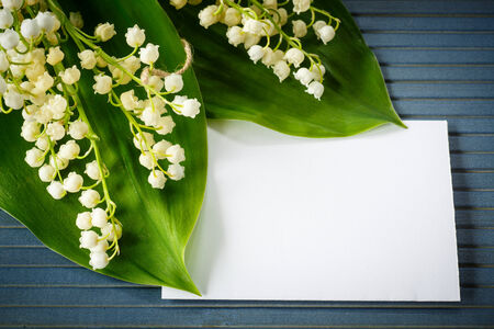 bouquet of lilies of the valley on a blue rustic table photo