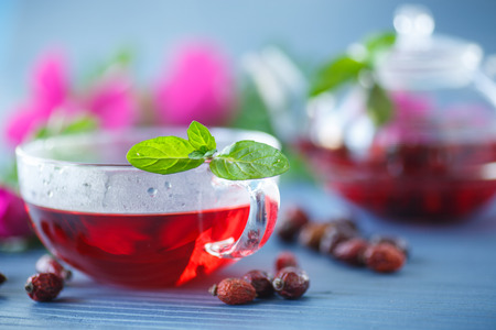 rosehip tea with fruits and flowers in a teapot on the table photo
