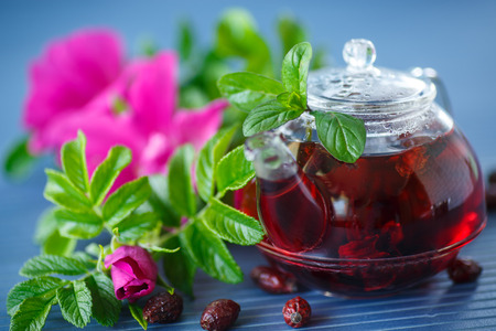 rosehip tea with fruits and flowers in a teapot on the table