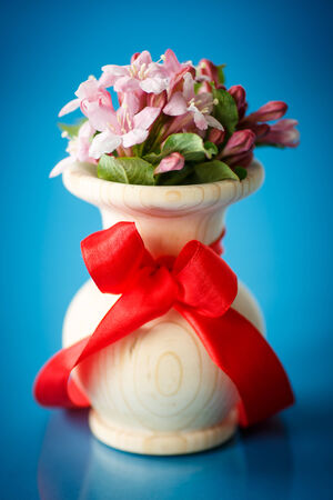 Weigela blooming beautiful wood vase on the table photo