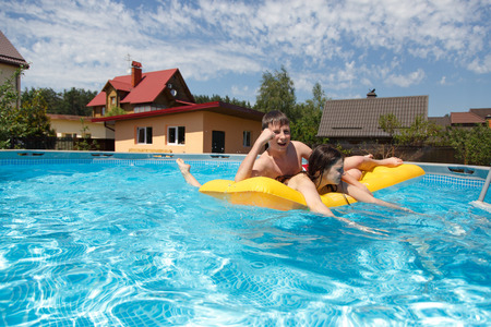 Two teenagers swimming in the pool in the hot summer photo