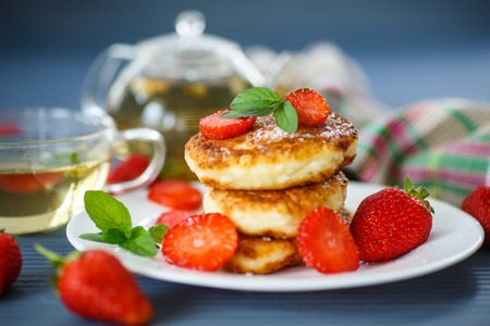curd cheese pancakes fried with sugar and strawberries on a plate