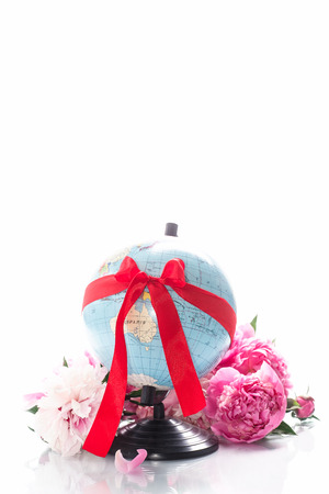 Globe tied with a ribbon and flowers on a white background photo