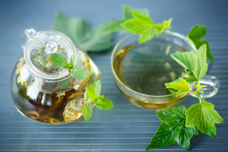 tea with currant leaves on a wooden table photo