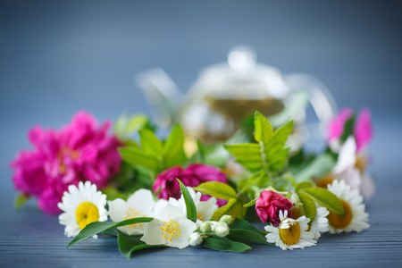 flower tea of different flowers in a teapot on the table photo