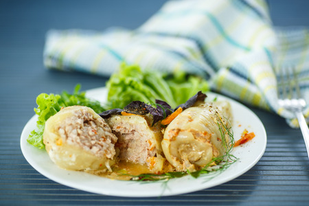 peppers stuffed with meat on a plate with greens photo