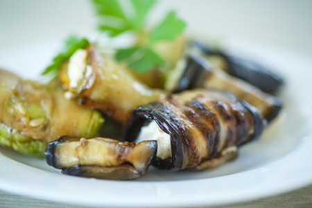 Aubergine rolls with cheese filling on a plate photo